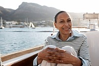 Woman sitting in boat, harbour and hills in background