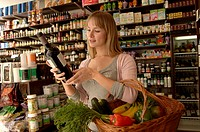 Female customer in delicatessen choosing wine