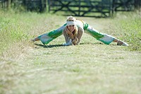 Young woman doing splits in rural field, smiling at camera