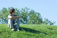 Teen boy sitting on grassy hill, relaxing