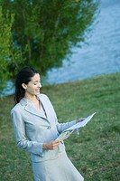 Businesswoman reading newspaper in park