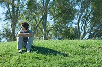 Teen boy sitting on grassy hill, relaxing (thumbnail)