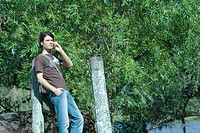 Casual man leaning against post, using cell phone