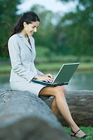 Businesswoman sitting on tree trunk using laptop