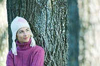 Young woman wearing knit hat, leaning against tree, smiling