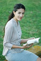 Young woman sitting outdoors, reading book