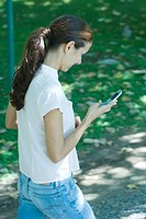 Woman walking through park, looking at cell phone