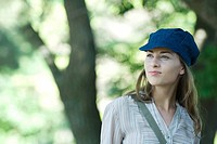 Young woman walking through park, wearing cap