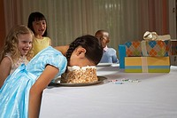 Four children 5-8 at table, laughing at girl with face in cake