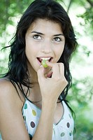 Woman biting into grape, looking up