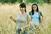 Young female hikers walking through field