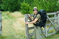 Hiker standing next to wooden gate