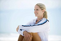 Young woman in active wear, sitting on beach, knees up, smiling