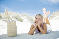 Young woman lying on beach, beach bag nearby (thumbnail)
