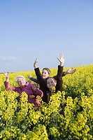 Senior woman and two granddaughters standing in field of canola in bloom, striking poses