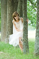 Young woman wearing dress, peeking around tree
