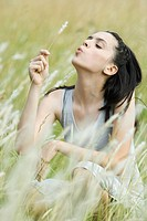 Teen girl sitting in field, holding sprig of long grass