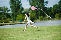 Teen girl running with kite, full length