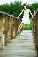 Teen girl lifting self up on railing of wooden bridge, smiling at camera