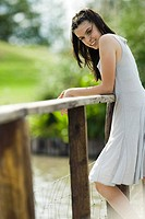 Teen girl leaning against wooden railing outdoors, smiling at camera