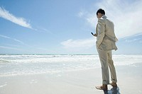 Businessman standing barefoot on beach, holding cell phone