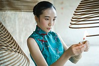 Young woman dressed in traditional Chinese clothing lighting spiral incense