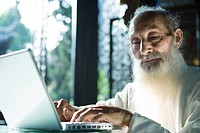 Elderly man in traditional Chinese clothing using laptop computer