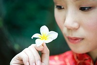 Young woman dressed in traditional Chinese clothing, holding up flower, close-up