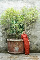 Young woman dressed in traditional Chinese clothing, standing next to potted tree