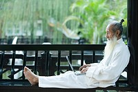 Elderly man in traditional Chinese clothing, barefoot, using laptop