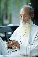 Elderly man in traditional Chinese clothing listening to MP3 player