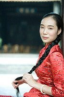 Young woman dressed in traditional Chinese clothing, holding her long braided hair, looking at camera