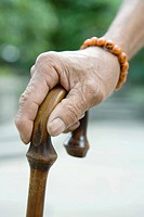 Elderly man holding cane, close-up of hand