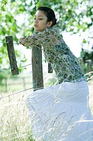 Young woman leaning against rural fence, looking away