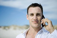 Man using cell phone, dunes in background, portrait