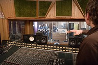 Producer signalling to band in recording studio