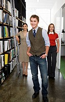 Young businesspeople next to bookshelves