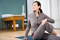 Asian woman stretching on yoga mat