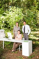 Businesspeople next to desk in woods