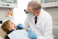Male dentist examining boy