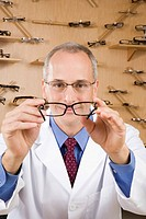 Male optician holding eye glasses