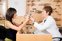 Female optician giving eyeglasses to woman
