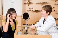Woman trying on eyeglasses in opticianÆs office