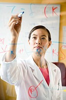 Asian female scientist writing on clear board