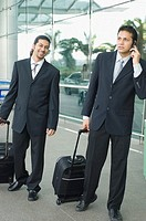 Two businessmen standing at an airport and waiting