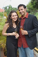 Portrait of a young couple holding champagne flutes and smiling