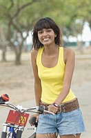 Portrait of a young woman standing with a bicycle and smiling