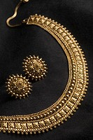 Close-up of a golden necklace with earrings