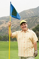 Mature golfer holding flag stick