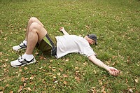 Man resting on grass with hat covering face